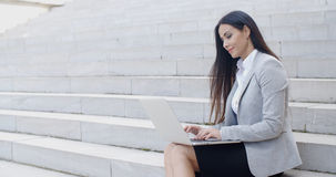 Smiling woman using laptop on stairs Royalty Free Stock Photos