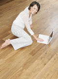 Smiling Woman Using Laptop On Wood Flooring Royalty Free Stock Image