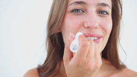 Smiling woman using lip balm for her lips stock footage