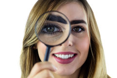 Smiling woman using magnifying glass Stock Images