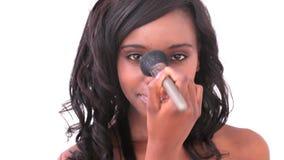 Smiling woman using makeup brush Stock Photos