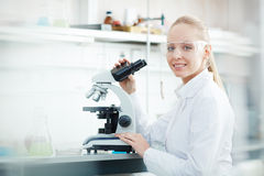 Smiling Woman Using Microscope in laboratory. Side view portrait of beautiful blond woman using microscope and looking at camera while working on research in Royalty Free Stock Photos
