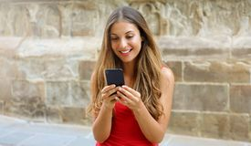 Smiling woman using mobile phone app to play video games online. City woman relaxing. Urban lifestyle. Banner crop for advertising. Copy space, background royalty free stock image