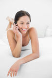 Smiling woman using mobile phone in bed Stock Photography