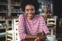 Smiling woman using mobile phone in cafe Royalty Free Stock Image