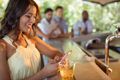 Smiling woman using mobile phone while having a glass of beer Royalty Free Stock Photos