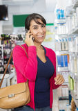 Smiling Woman Using Mobile Phone In Pharmacy Royalty Free Stock Image