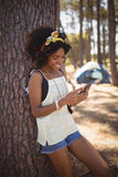 Smiling woman using mobile phone while standing against tree Royalty Free Stock Photography