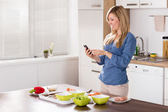 Smiling Woman Using Mobilephone In Kitchen. Smiling Young Woman Using Mobilephone While Standing In Kitchen Stock Photography
