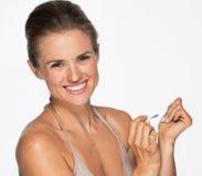 Smiling woman using nail polish Royalty Free Stock Images