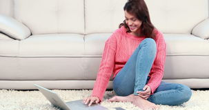 Smiling woman using phone and laptop. In the living room stock video footage