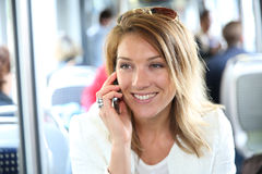 Smiling woman using public transport talking on the phone Stock Photo