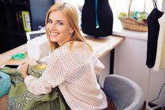 Smiling woman using a sewing machine Stock Photography