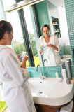 Smiling woman using skin care lotion bathroom Royalty Free Stock Photo