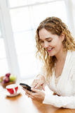Smiling woman using smart phone Royalty Free Stock Photos