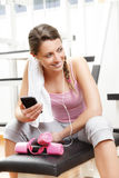 Smiling woman using smart phone at the gym Stock Photography