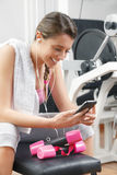Smiling woman using smart phone at the gym Royalty Free Stock Photos