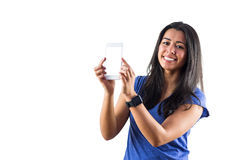 Smiling woman using a smartphoen and wearing a smartwatch Royalty Free Stock Photography