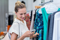 Smiling woman using smartphone while browsing clothes Royalty Free Stock Photo