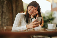 Smiling woman using smartphone in cafe Royalty Free Stock Image