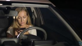 Smiling woman using smartphone in car at night stock video