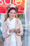 Smiling woman using smartphone in front of window Royalty Free Stock Photography