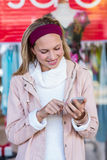 Smiling woman using smartphone in front of window Stock Photo