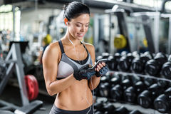 Smiling Woman Using Smartphone in Gym Stock Photo