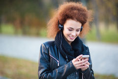 Smiling woman using smartphone with headphones Royalty Free Stock Image