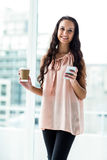 Smiling woman using smartphone holding disposable cup Royalty Free Stock Photo