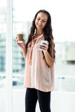 Smiling woman using smartphone holding disposable cup Stock Photos