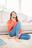 Smiling woman using smartphone while sitting on floor Royalty Free Stock Photography