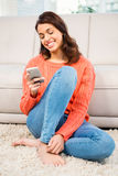 Smiling woman using smartphone while sitting on floor Royalty Free Stock Photos
