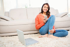 Smiling woman using smartphone while sitting on floor Stock Images