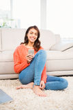 Smiling woman using smartphone while sitting on floor Royalty Free Stock Photo
