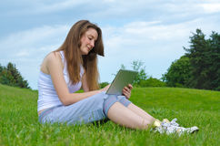 Smiling woman using a tablet Stock Photography