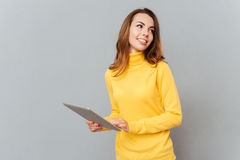 Smiling woman using tablet computer and looking away at copyspace. Smiling young woman using tablet computer and looking away at copyspace  on a gray background Royalty Free Stock Photos
