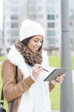 Smiling woman using tablet computer, outdoor. Royalty Free Stock Image