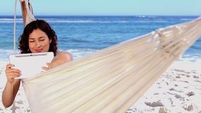 Smiling woman using tablet in a hammock Stock Image