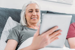 Smiling woman using tablet while lying in bed at home Royalty Free Stock Photo