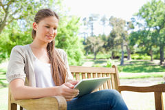 Smiling woman using a tablet on a park bench Stock Photography