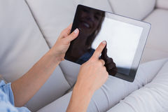 Smiling woman using tablet pc on couch Royalty Free Stock Photography