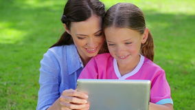 Smiling woman using a tablet pc with her daughter stock footage