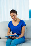 Smiling woman using tablet on sofa royalty free stock photo