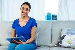 Smiling woman using tablet on sofa stock image