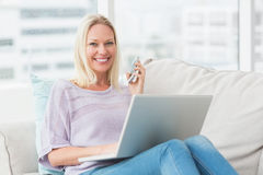 Smiling woman using technologies on sofa Royalty Free Stock Image