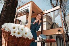 Smiling woman using telephone box on the street royalty free stock images