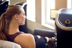 Smiling woman using weight machine Stock Image
