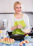 Smiling woman using whisk Royalty Free Stock Photography