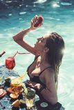 Smiling woman on vacation holiday in the villa pool holding delicious cocktail and fruit. stock photos
